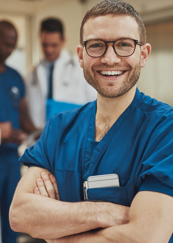 Smiling optimistic young male hospital surgeon standing in front of his colleagues with folded arms beaming at the camera
